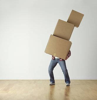 A man carrying three cardboard boxes trying to find the right moving boxes that will help him move