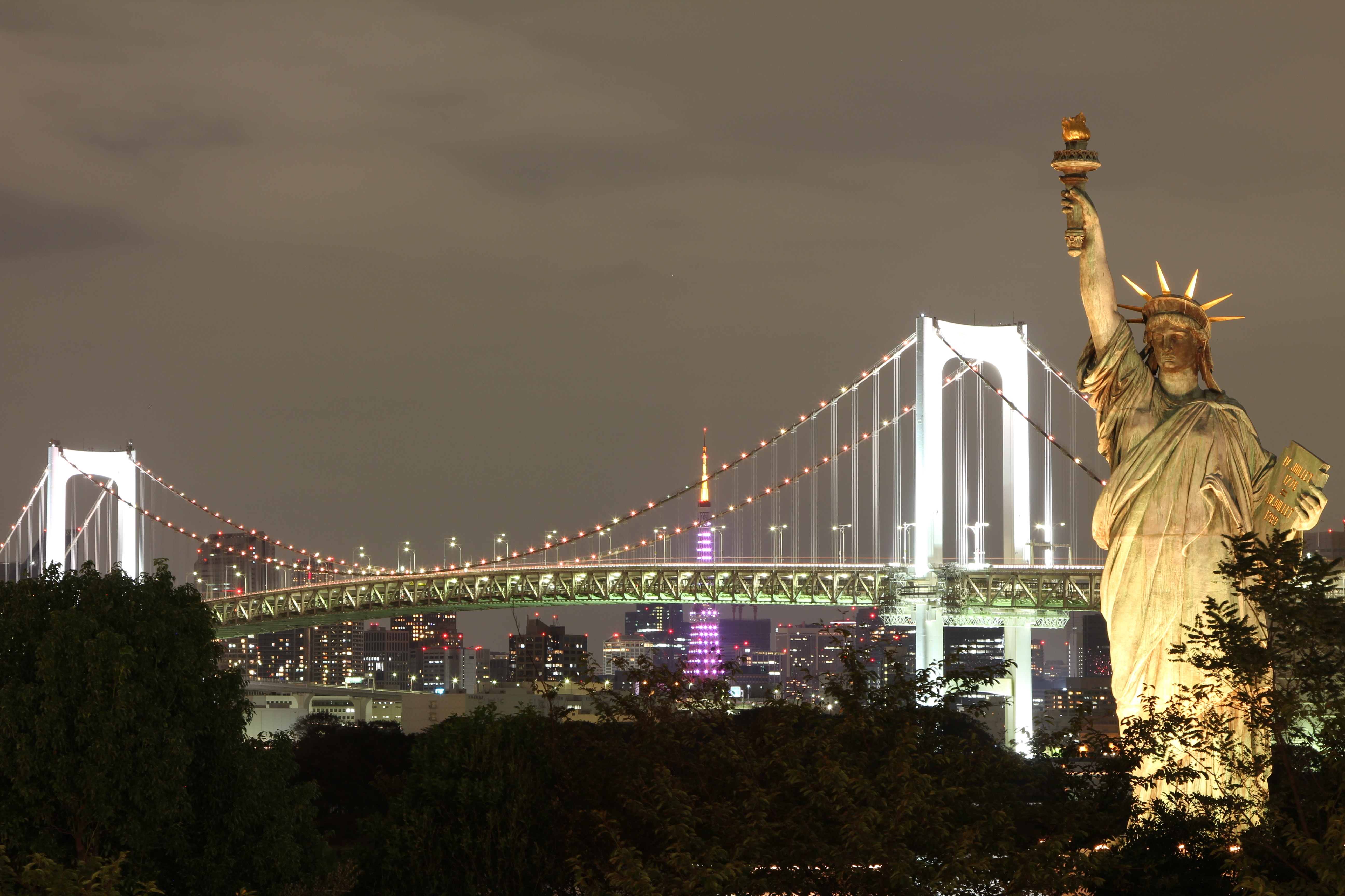 The night view of the Statue of Liberty and Brooklyn bridge you'll get a chance to see after Investing in NYC rental real estate