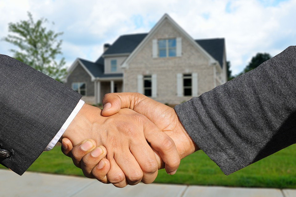 two man shaking hands and a house in the background