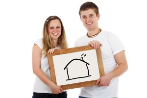Couple holding a board with a drawing of a house.