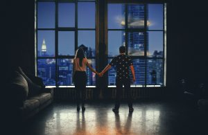 Couple holding hands and looking out of their NYC apartment.